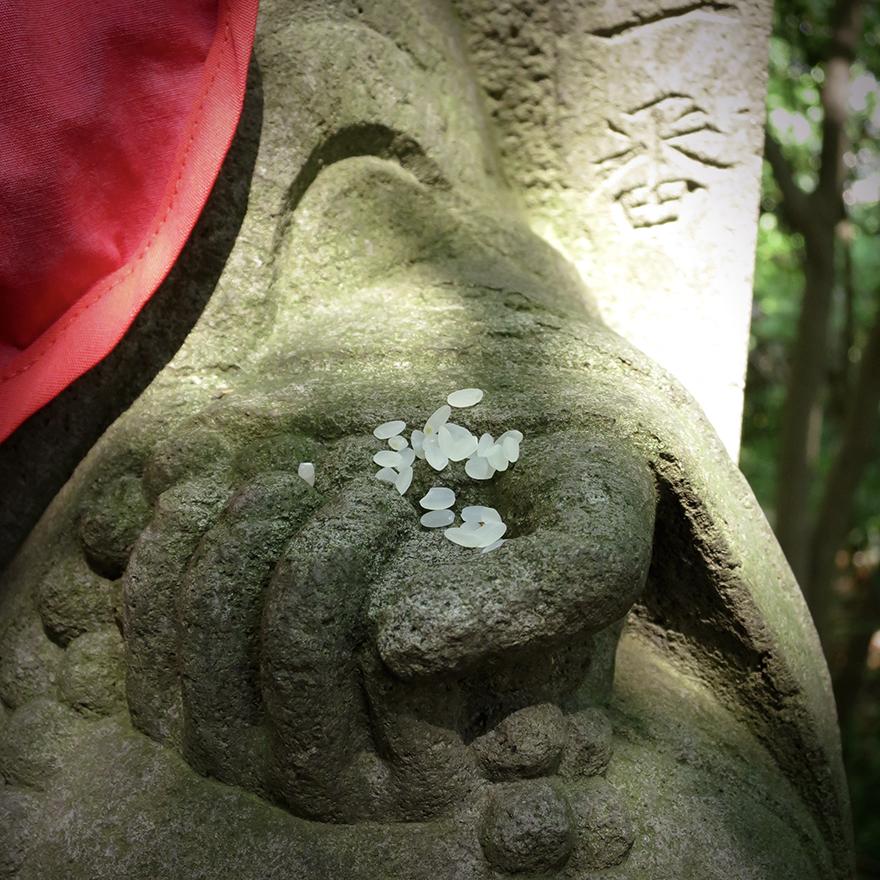 Rice offering left by pilgrim at Jizo figure on pilgrimage hike at Takahata Fudo-san