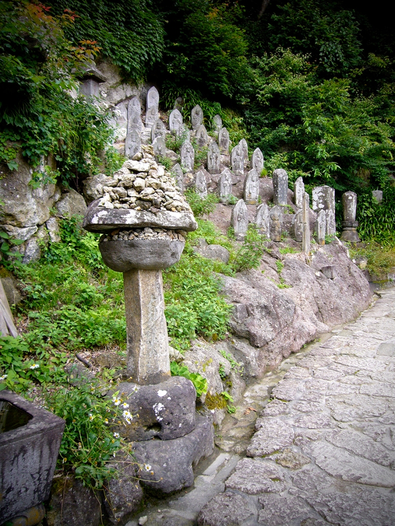 Jizo figures and stones left by pilgrims on climb to Yamadera in Yamagata