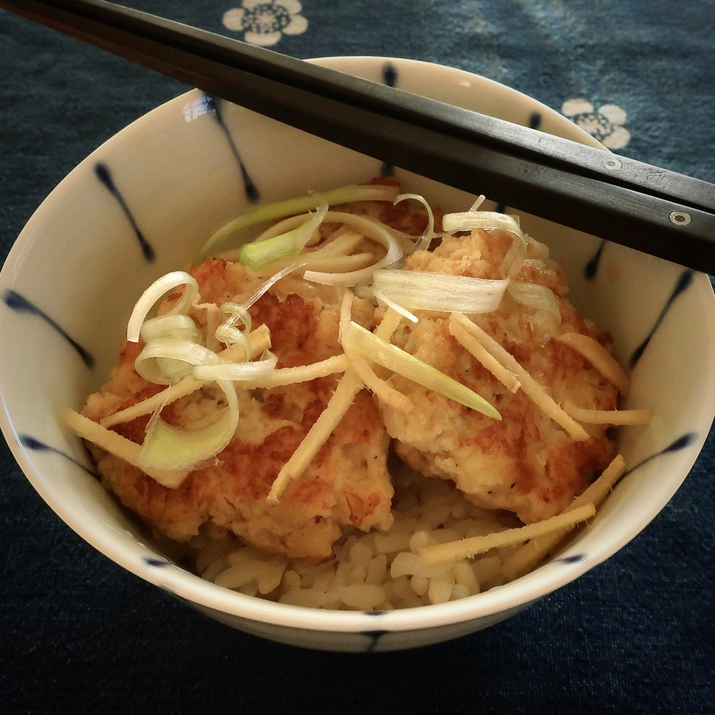 Japanese bowl and chopsticks with rice and chicken mini-burgers topped with slivered ginger and green onions