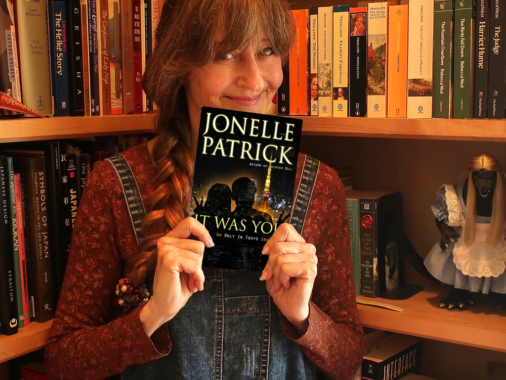 Author Jonelle Patrick holding a paperback copy of It Was You, an Only In Tokyo Short