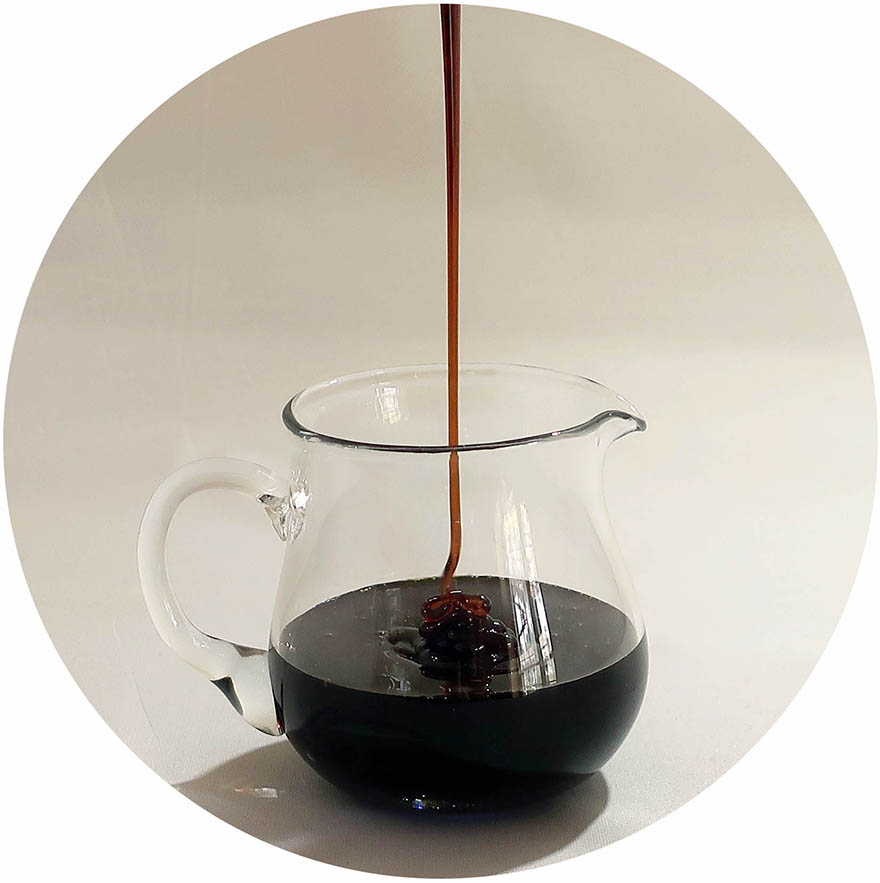 Photo of kuromitsu Okinawan black sugar syrup drizzling into a clear pitcher
