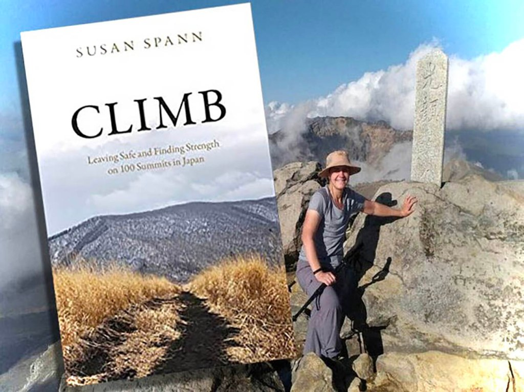 Author Susan Spann on a mountaintop with the covr of her memoir CLIMB