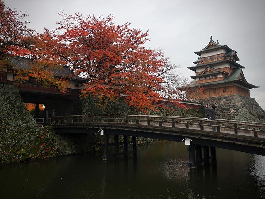 Autumn leaves frame bridge over moat at Takashima castle in Suwa City Nagano