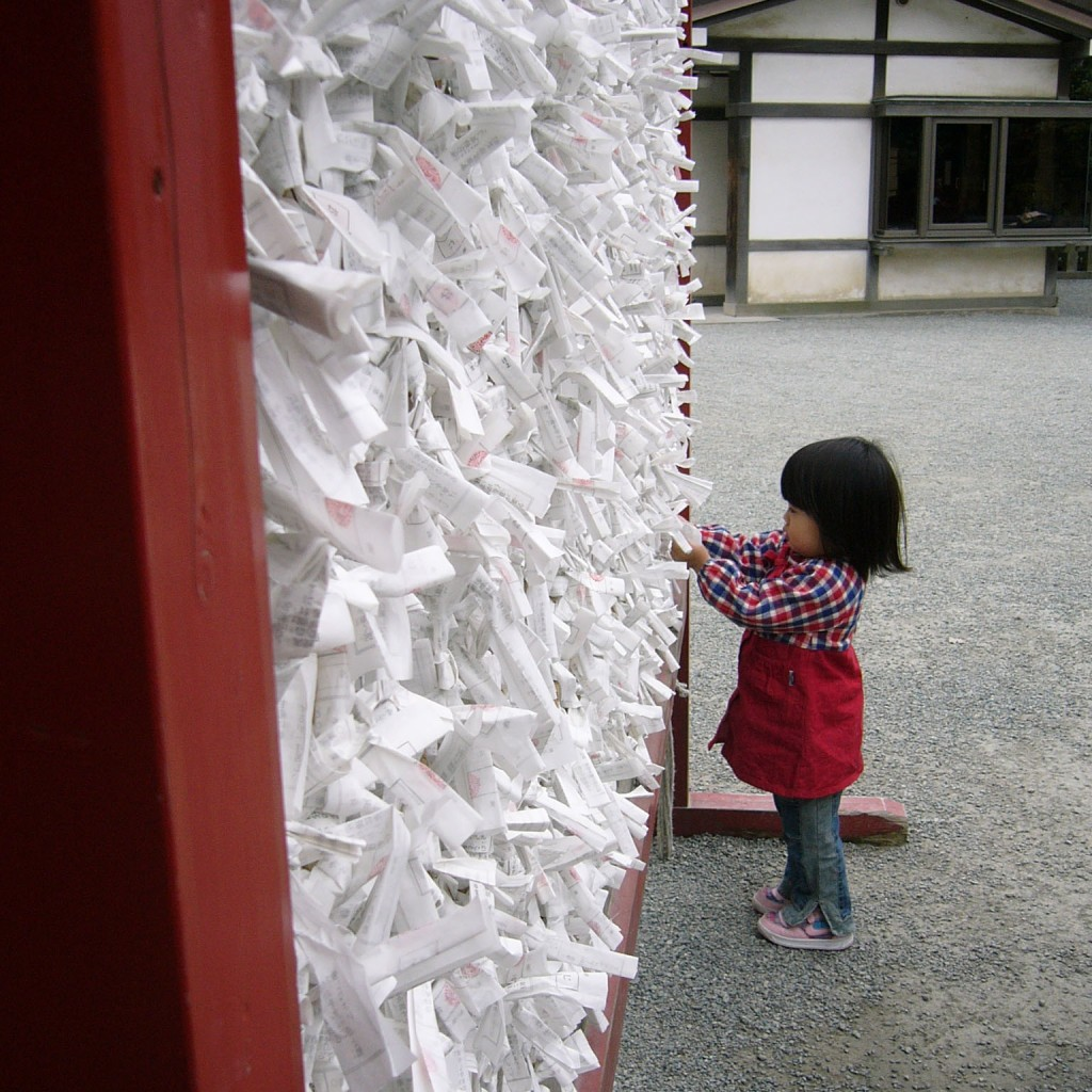 Little girl tying an o-mikuji fortune onto a rack at the Tsurugaoka Hachimangu Shrine in Kamakura