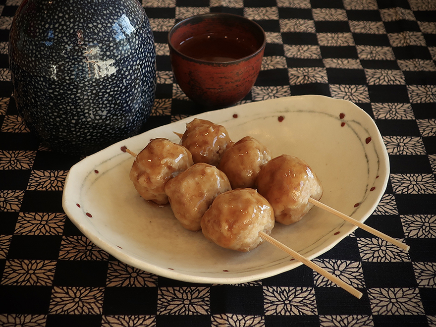Chicken meatball tsukune on a plate with a cup of sake