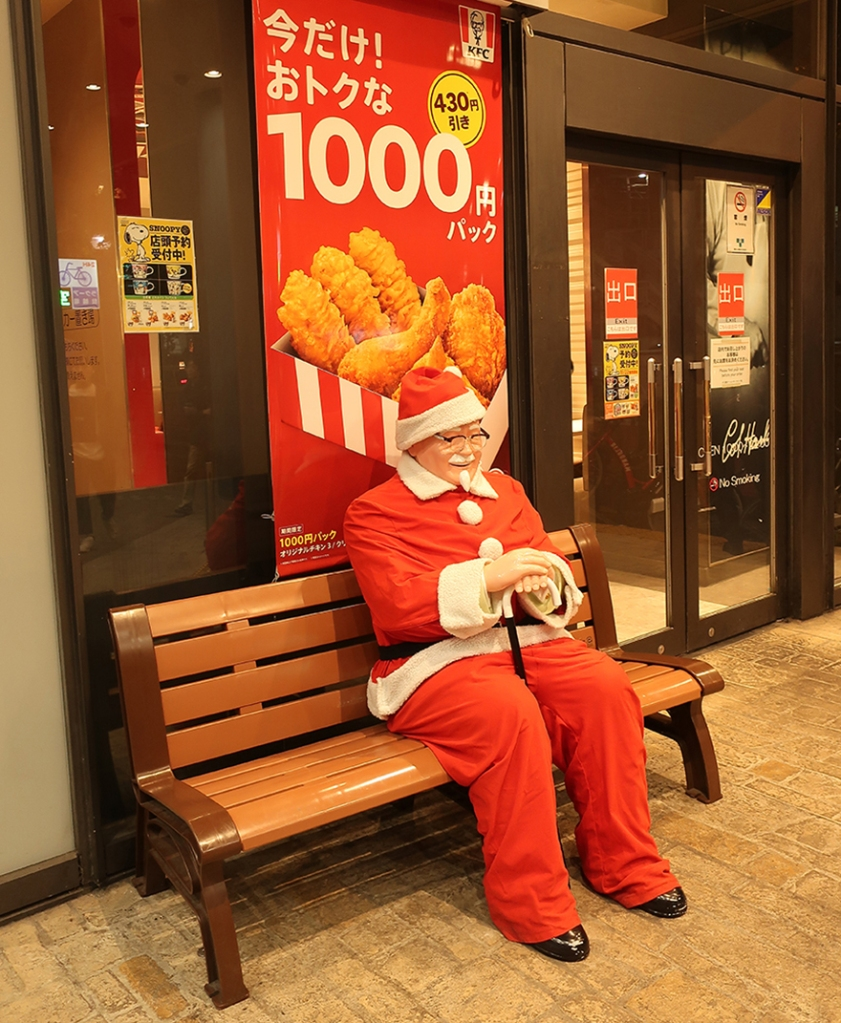 Colonel Sanders dressed as Santa outside KFC