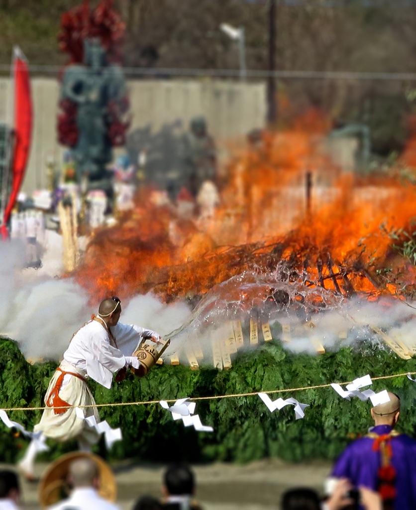 Monk throwing water on bonfire at Mt. Takao Hiwatari Matsuri