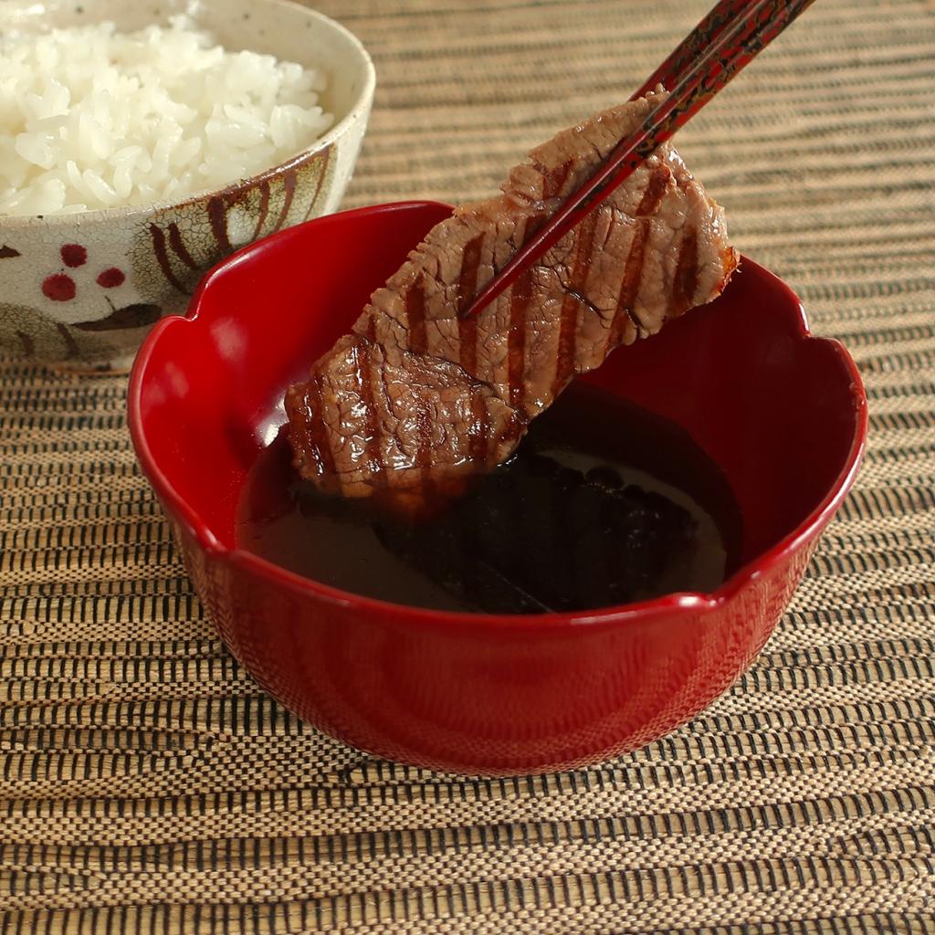 Dipping slice of steak in Japanese ginger-soy steak dipping sauce