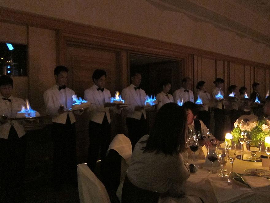 Waiters serving flaming Baked Alaska at a Japanese wedding