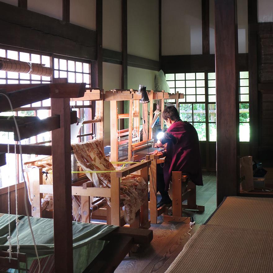 Volunteer demonstrating weaving in a thatch-roofed farmhouse at the Nihon Minka-en Japanese Folk House Garden