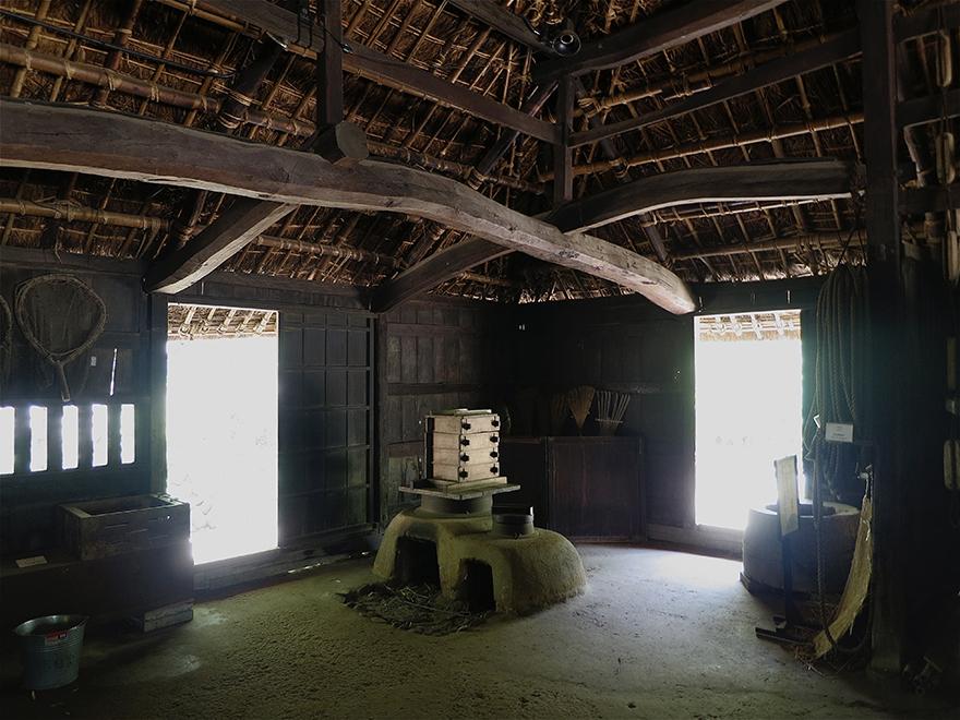 Kitchen interior of a thatch-roofed farmhouse at the Nihon Minka-en Japanese Folk House Garden
