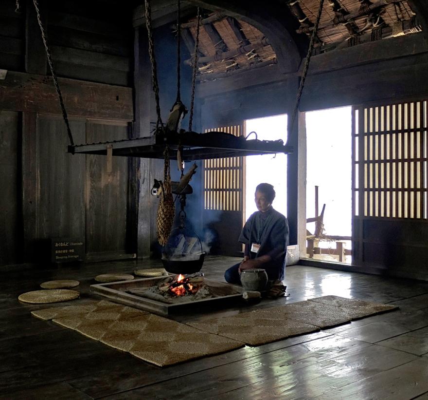 Volunteer tending the hearth in the interior of a thatch-roofed farmhouse at the Nihon Minka-en Japanese Folk House Garden