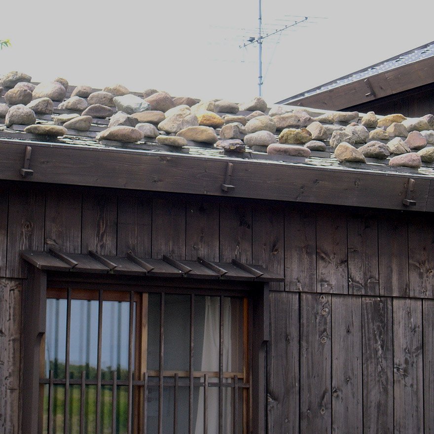 Rock weighing down a roof on Sado Island