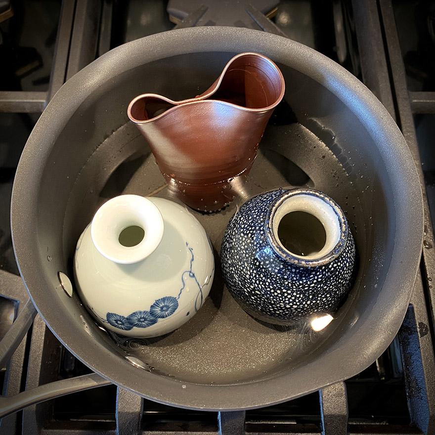 Warming sake in flasks in a saucepan